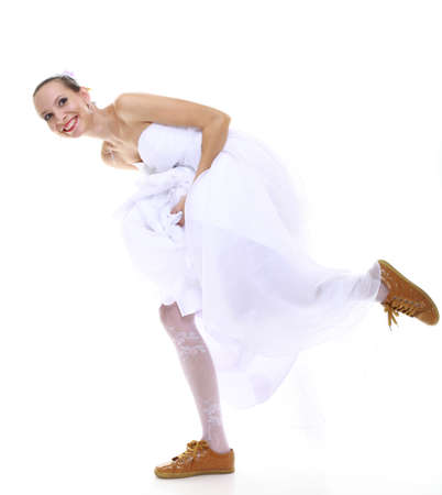 Wedding day. Running bride funny young woman wearing sporting shoes isolated on white background photo