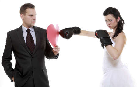 Bad relationship. Funny wedding couple expressive fighting. Woman showing her husband whos boss. Angry wife boxing husband. Isolated on white photo