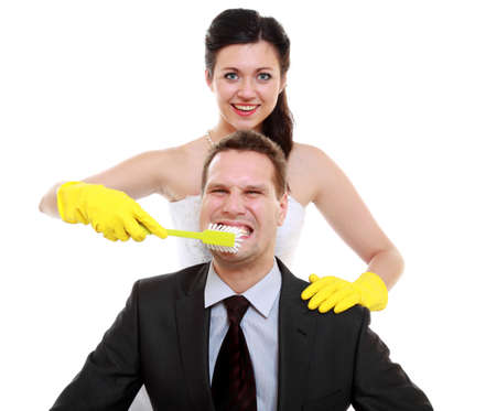 emancipation: Emancipation idea concept. Humorous funny wedding couple bride and groom - woman brushing teeth of her man, show her domination, taking control isolated