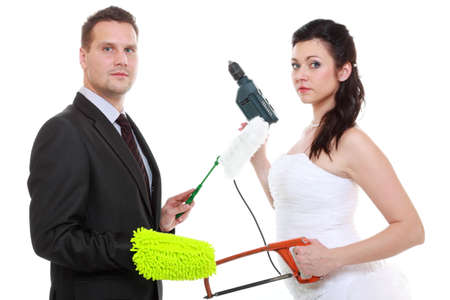 emancipation: Feminism emancipation concept. Humorous funny couple bride groom in domestic role, sharing household chores. Woman with male tools, man with cleaning cloth isolated on white background