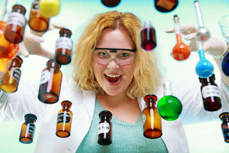 Crazy chemist woman or girl student or female laboratory assistant or scientific researcher with chemical glassware test flask. Experiment, research in progress, green background photo