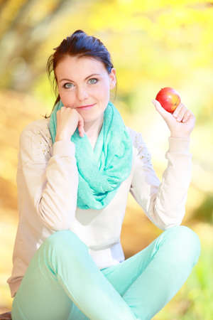 Fall lifestyle concept, harmony freedom. Casual young woman girl relaxing in autumnal park eating red apple. Golden colorful leaves background photo