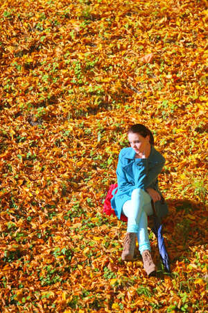 Young  thoughtful pensive woman outdoor, sad unhappy girl thinking in the autumn park. Loneliness stress depression. photo