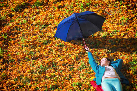 Fall lifestyle concept. Casual young woman girl relaxing with blue umbrella in autumnal park. Golden colorful leaves background photo