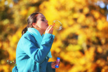 Happiness carefree and autumn. Young woman having fun blowing soap bubbles in park on a bright yellow leaves background photo