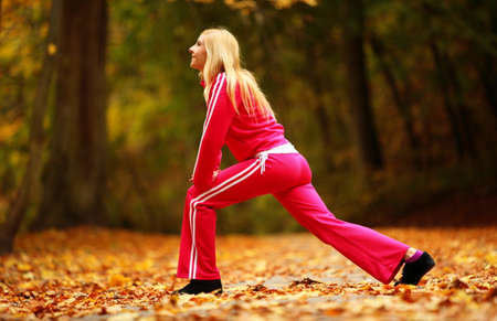 Healthy active lifestyle. Fitness woman doing exercise outdoor, cross training workout. Young blonde girl fit fitness sport female outside in autumn fall park. photo
