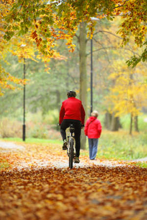 Healthy active lifestyle, cycling outdoors man exercising with bicycle riding a bike, golden autumn fall leaves in park photo