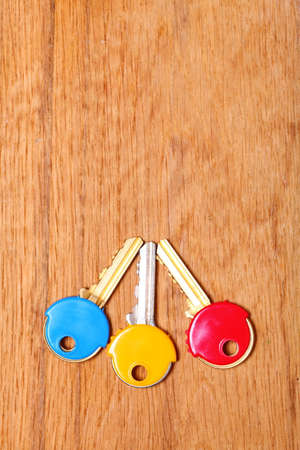 house coats: Three house keys with colorful plastic coats caps on wooden table background. Copy space for text