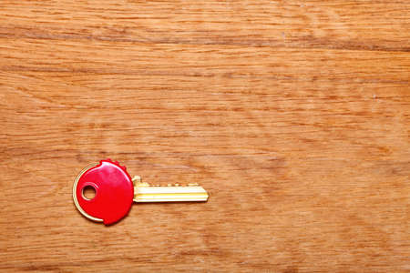 house coats: House key with red plastic coats caps on wooden table background. Copy space for text
