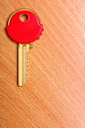 House key with red plastic coats caps on wooden table background. photo