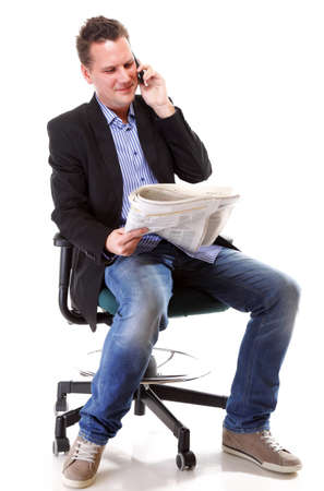 Full length businessman reads newspaper phoning talking on mobile phone commenting economy news isolated on white background photo