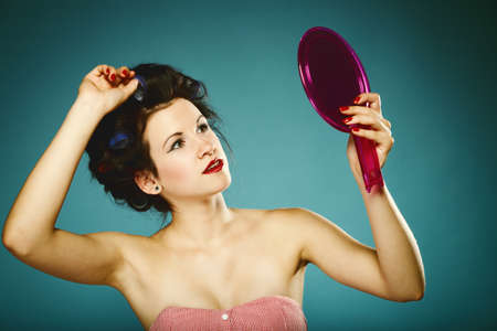 young woman preparing to party having fun, girl styling hair with curlers looking in the mirror retro style blue background photo