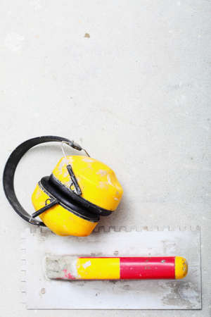 notched: Ear hearing protection. Yellow working protective headphones noise muffs, and notched trowel, toolwork in construction site