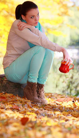 Young thoughtful pensive woman in the autumn park relaxing enjoying hot drink coffee or tea, holding red mug with warm beverage. Yellow leaves background photo