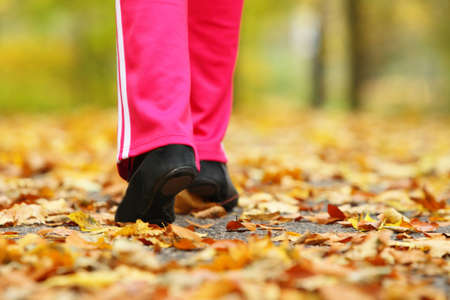 Runner legs and running shoes. Sporty woman jogging walking outdoors in autumn park on forest path, fall colors golden leaves photo