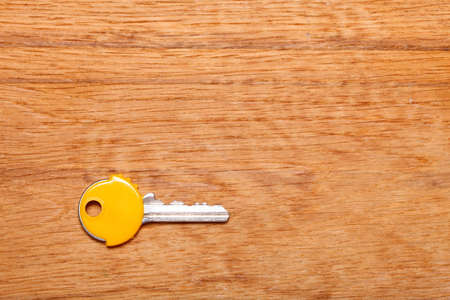 house coats: House key with yellow plastic coats caps on wooden table background. Copy space for text
