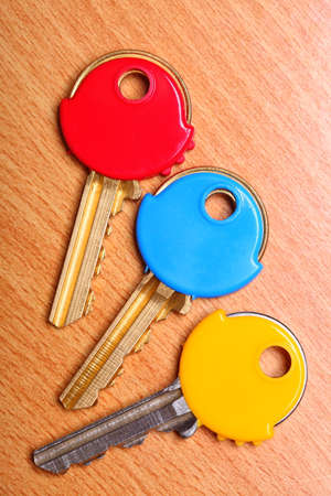 house coats: Three house keys with colorful plastic coats caps on wooden table background.