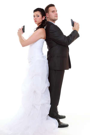 Bad relationship concept - married couple problem discord. Bride and groom with handgun. Man woman in disagreement. Isolated on white background photo