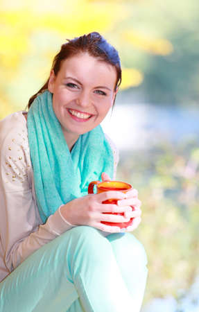 Happiness carefree and nature. Young happy woman relaxing in the autumn park enjoying hot drink coffee or tea, holding red mug with warm beverage.  photo