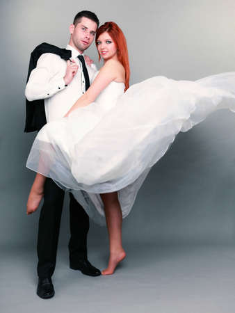 Wedding day. Portrait of happy married couple red haired bride and groom in full length studio shot  photo
