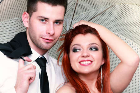 Wedding day. Portrait of happy married couple red haired blue eyed bride and groom with umbrella studio shot  photo