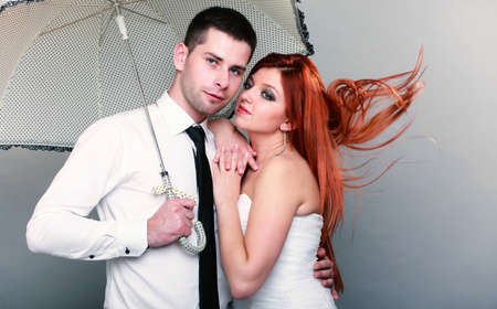 Wedding day. Portrait of happy married couple blue eyed bride with her red hair blowing in the wind and groom with umbrella studio shot  photo