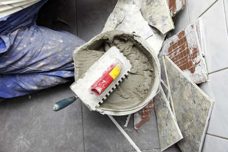 a tiler at work. bonding of floor tile with tile adhesive and filler. Stock Photo - 23126385