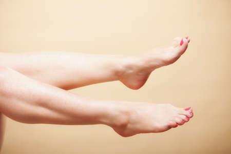 Beautiful perfect long naked woman girl legs barefoot body care pedicure on orange photo