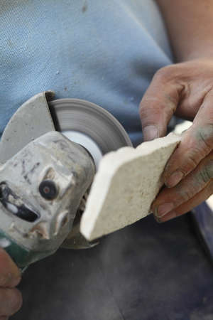 clinker tile: Renovation at home worker cuts tile with angle grinder electric tool man is tiling at home construction site
