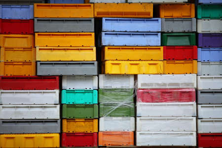 colorful boxes plastic crates background. Packing containers piles for fish storage of catch. photo