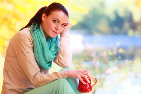 Young happy woman relaxing in the autumn park enjoying hot drink coffee or tea. photo