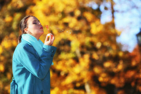 Young woman having fun blowing soap bubbles in park on a bright yellow leaves background photo