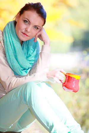Young happy woman relaxing in the autumn park enjoying hot drink coffee or tea, holding red mug with warm beverage.  photo