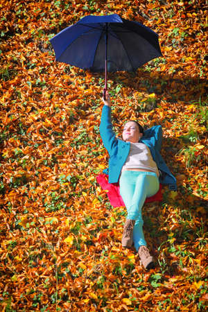 Casual young woman girl relaxing with blue umbrella in autumnal park. photo