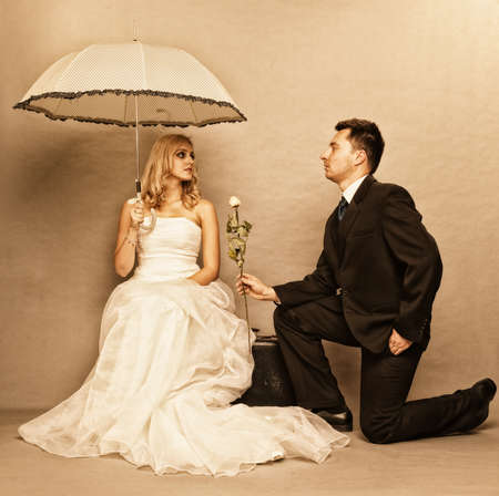 enamored: Wedding day. Portrait of romantic married couple blonde bride with umbrella and enamored groom giving a rose to girl. Full length studio shot sepia color, vintage photo