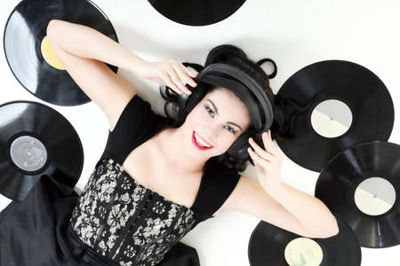 Sexy happy girl with phonography analogue record and headphones music lover retro style studio shot photo