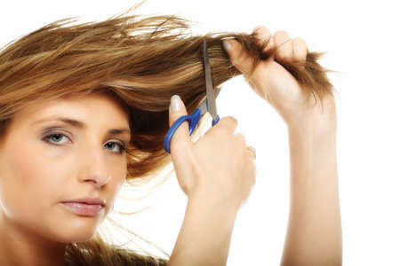 Damaged dry hair splitting ends. Young blonde woman cutting her hair with scissors - unhappy expression, isolated on white background photo
