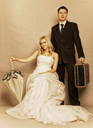 Wedding day. Portrait of married retro couple blonde bride with umbrella and groom with suitcase. Full length studio shot sepia color, vintage photo photo