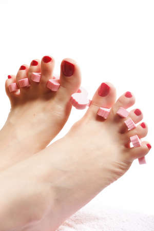 s�parateurs: pied p�dicure appliquant les pieds de la femme avec des ongles rouges dans s�parateurs d'orteils fond blanc