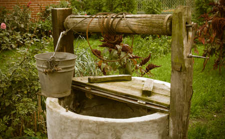 old rotten water well in sumer garden, rural scenery photo
