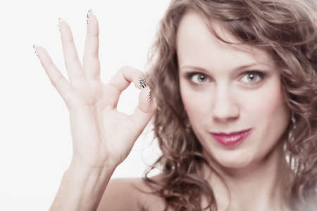 Happy satisfied woman gesturing the all right symbol, girl showing ok sign isolated on white background photo