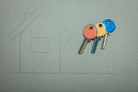 Hand drawn sketch house on recycled paper home symbol and colorful keys, real estate business & building concept. photo
