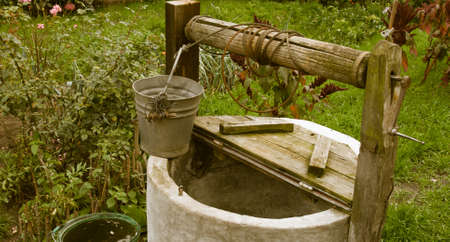water well: old rotten water well in sumer garden, rural scenery