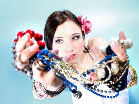 young woman in summer style with plenty of jewelry and beads in hands. photo