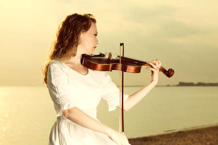 The blonde girl playing her violin at sunset. photo