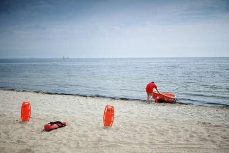 buoyancy: Lifeguard rescue equipment orange preserver tool and boat, red plastic buoyancy aid in the sand