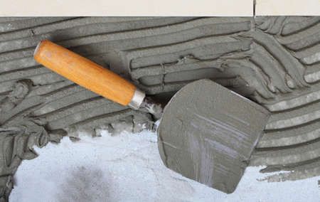 Home improvement, renovation construction trowel with cement mortar for tiles work, tile floor adhesive photo