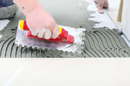 Home improvement, renovation - construction worker tiler is tiling, ceramic tile floor adhesive, trowel with mortar photo