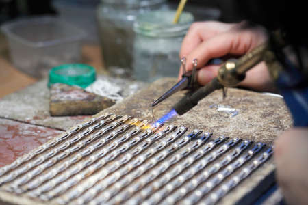 hands of jeweller at work silver soldering. Goldsmith working and welding. photo