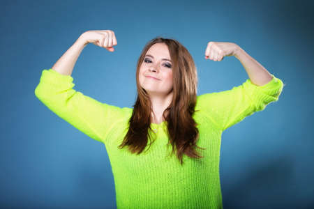 clenching fists: woman long hair clenching fists shows her muscles blue background strength and power concept Stock Photo